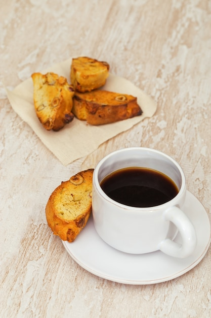 Italian dry homemade cookies cantucci on table and coffee in white cup. Premium Photo