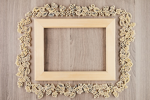 Italian dry sea pasta on beige brown wooden board with empty copyspace as decorative frame background Premium Photo