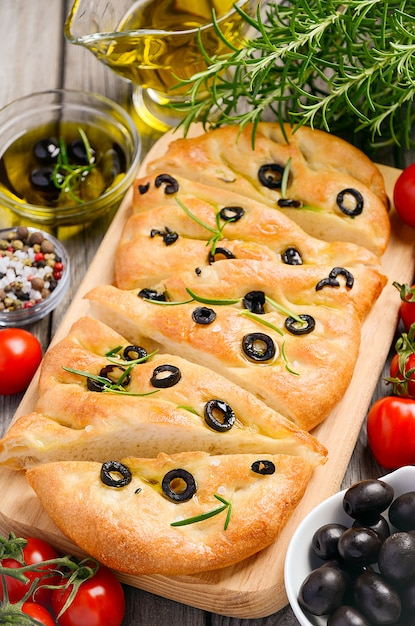 Italian focaccia bread with olives and rosemary on rustic wooden background. Premium Photo