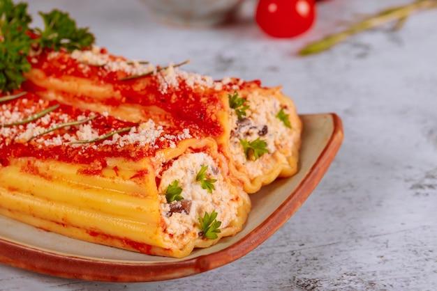 Итальянская еда каннеллони с рикоттой и томатным соусом. закройте Premium Фотографии