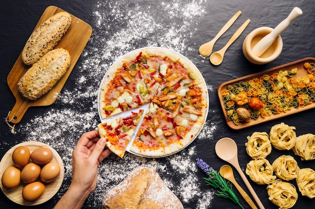 Italian food decoration with hand taking pizza slce Free Photo