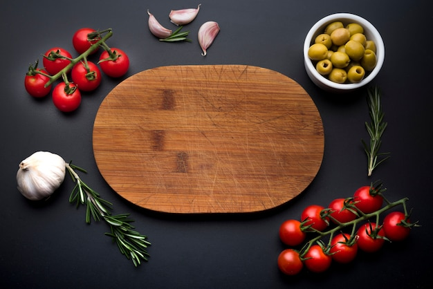 Italian food ingredients around empty wooden cutting board Free Photo