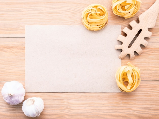 Italian foods concept and menu design blank paper and  pasta ladle on wooden. Premium Photo