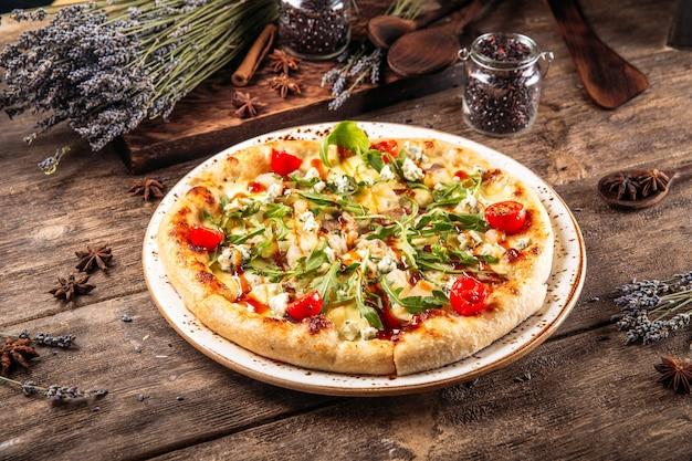 Итальянская свежеиспеченная пицца из пушистого теста с рукколой и помидорами на деревянном столе Premium Фотографии