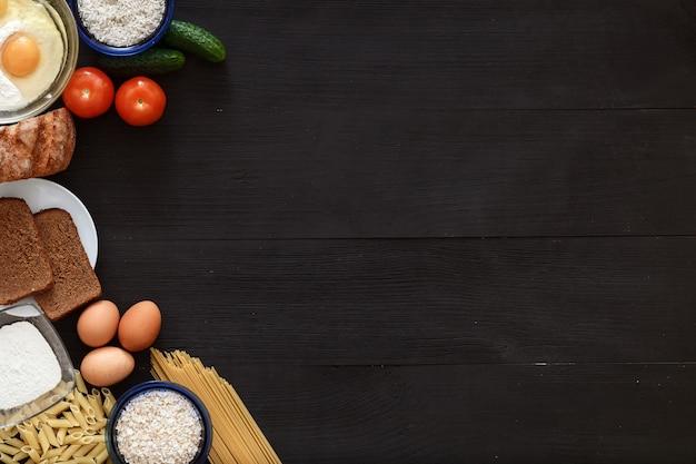 Итальянская здоровая еда стол, овощи спагетти на черном деревянном столе, вид сверху Premium Фотографии