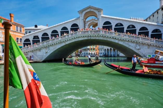 Итальянский морской флаг с мостом риальто с гондолами в заднем. большой канал, венеция, италия Premium Фотографии