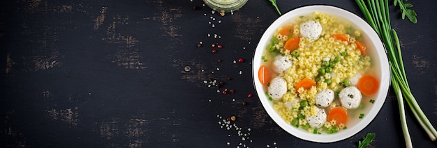 Italian meatball soup and stelline gluten free pasta in bowl on black table Free Photo