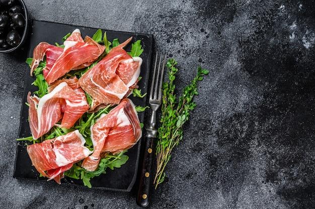 Italian parma prosciutto crudo dried ham on a marble board. black table. top view. copy space. Premium Photo