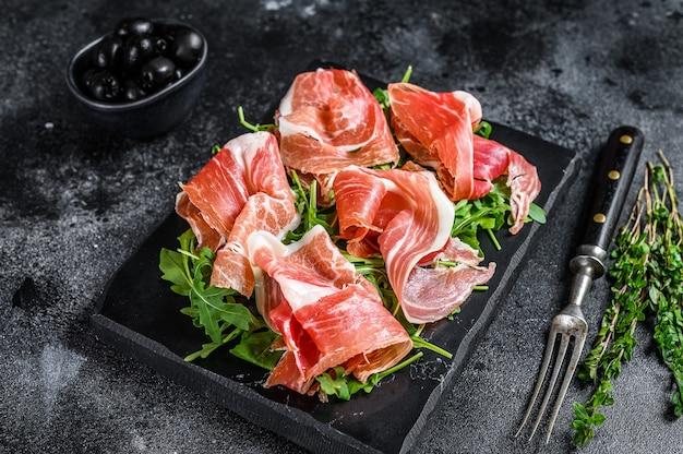 Italian parma prosciutto crudo dried ham on a marble board. black table. top view. Premium Photo