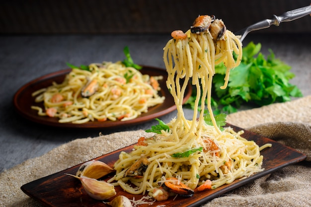 Italian pasta in a creamy sauce with seafood, shrimps and mussels on a plate Premium Photo