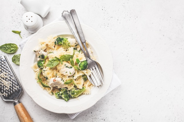 Italian pasta farfalle with broccoli, chicken and cheese in a white plate. Premium Photo