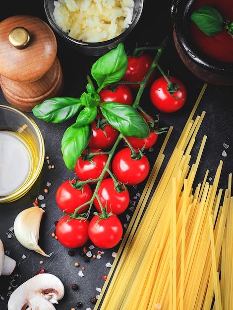 Italian pasta ingredients. cherry-tomatoes, spaghetti pasta, garlic, mushroom, basil, olive oil, mozzarella and spices on dark grunge backdrop Premium Photo