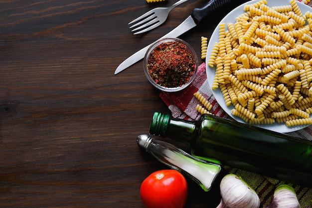 Italian pasta, olive oil, spices on a dark wooden table Premium Photo