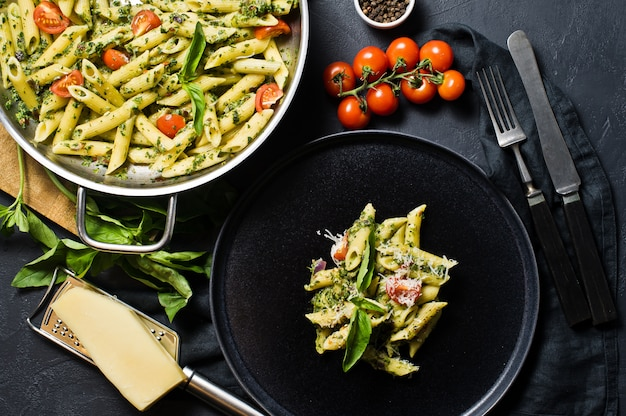 Italian pasta penne with spinach, cherry tomatoes and basil. Premium Photo