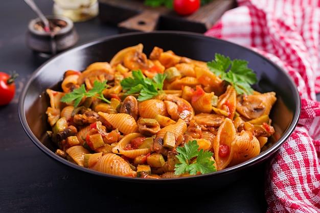 Italian pasta shells with mushrooms, zucchini and tomato sauce. Premium Photo