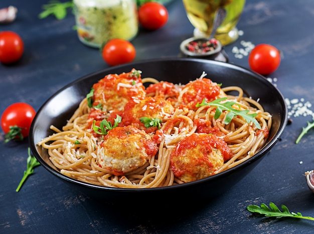 Italian pasta. spaghetti with meatballs and parmesan cheese in black plate on dark rustic wood background. dinner. slow food concept Free Photo