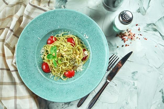 イタリアのパスタスパゲッティとペストソースとトマトの青い皿にキッチン用品のコンポジションで Premium写真