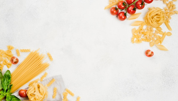 Italian pasta and tomatoes on desk Premium Photo