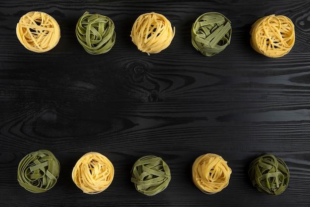 黒いテーブルの上のイタリアのパスタの品種 無料写真