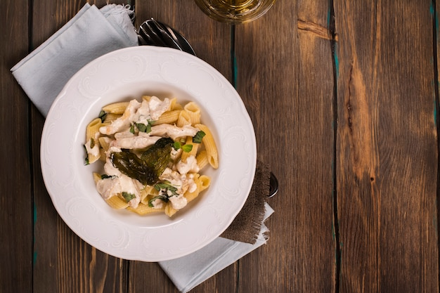 Italian pasta with chicken, cream sauce and basil over grunge wooden table. Premium Photo