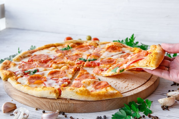 Italian pizza pepperoni on a light wooden Premium Photo