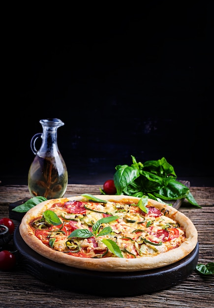 Italian pizza with chicken, salami, zucchini, tomatoes and herbs Free Photo