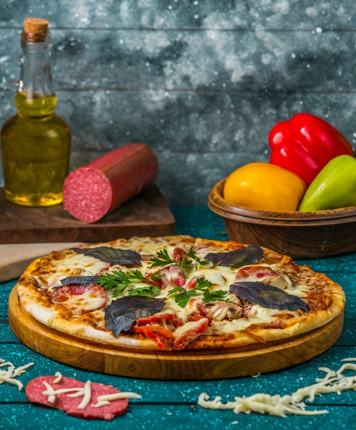Italian pizza with sausage, bell pepper garnished with dark opal basil and parsley Free Photo