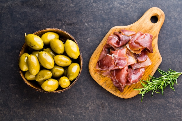 Italian prosciutto crudo or jamon with spice, olive, rosemary. raw ham. Premium Photo