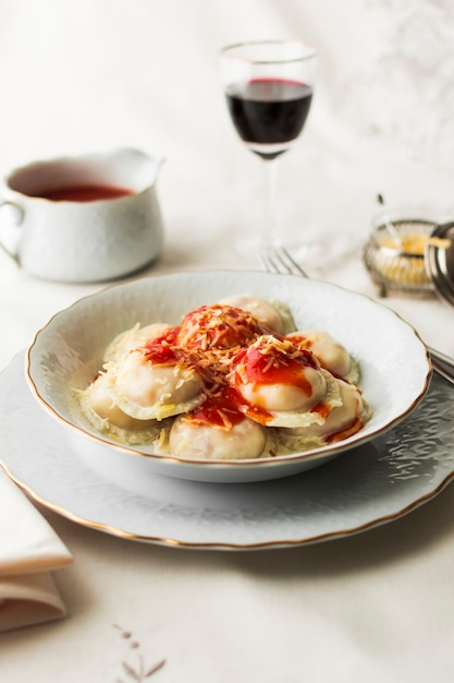 Italian ravioli pasta with spicy tomato sauce and cheese in bowl Free Photo