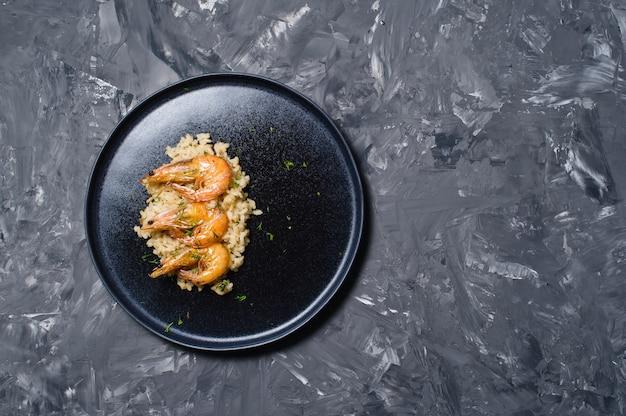 Italian risotto with shrimp on a black plate. Premium Photo