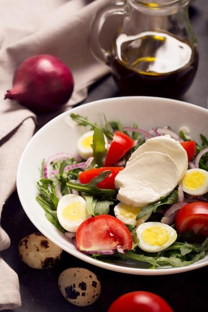 Italian salad prepared with arugula, mozzarella, eggs. black background Premium Photo