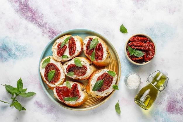 イタリアのサンドイッチ-ブルスケッタとチーズ、ドライトマト、バジル。 無料写真