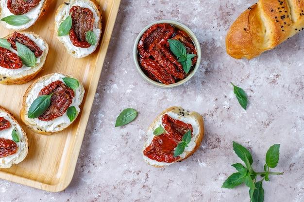 Итальянские бутерброды - брускетта с сыром, сушеными помидорами и базиликом Бесплатные Фотографии