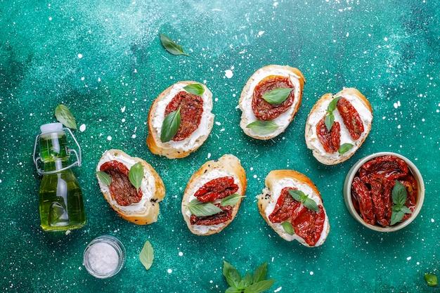イタリアのサンドイッチ-チーズ、ドライトマト、バジルのブルスケッタ。 無料写真