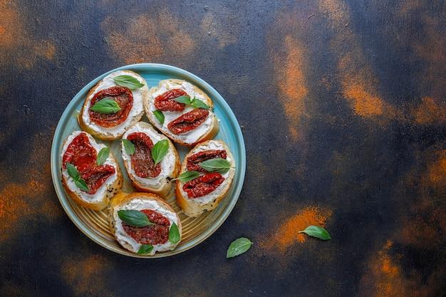 Italian sandwiches - bruschetta with cheese, dry tomatoes and basil. Free Photo