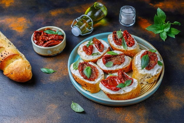 Italian sandwiches - bruschetta with cheese, dry tomatoes and basil. Free Photo