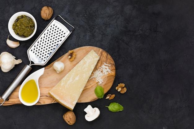 Italian sauce; cheese block; olive oil; walnut; garlic clove; basil and mushroom on stainless steel grater Free Photo