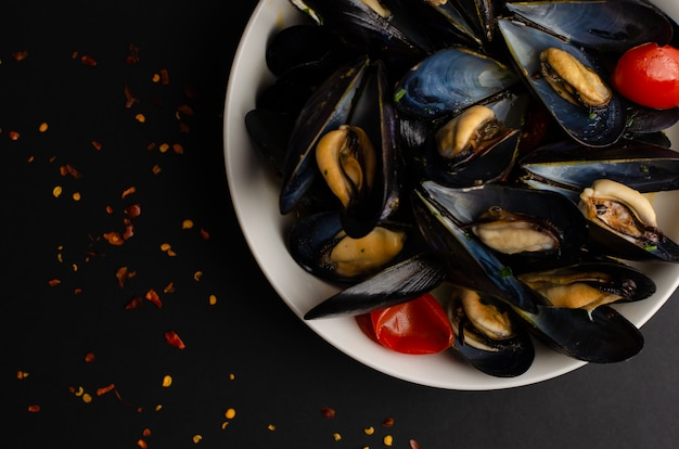 Italian seafood delicacy. mussel soup steamed in wine with tomatoes and hot peppers on black background. overhead shot, copy space Premium Photo