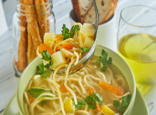 Italian soup with spaghetti, carrots, lemon, parsley and pieces of chicken in a green plate, on a table with napkins, spoons of bread and a drink in a glass Premium Photo