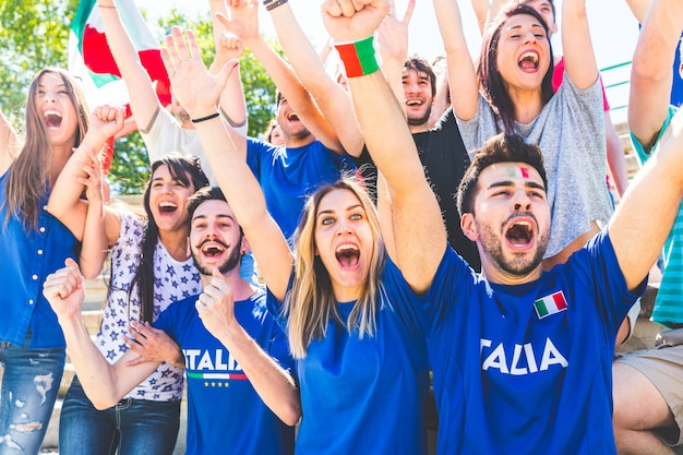 Italian supporters celebrating at stadium with flags Premium Photo