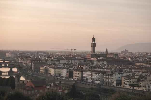 イタリア、長焦点レンズで、夕方の日没のアルノ川の遊び場とヴェッキオ宮殿からの眺め。 Premium写真