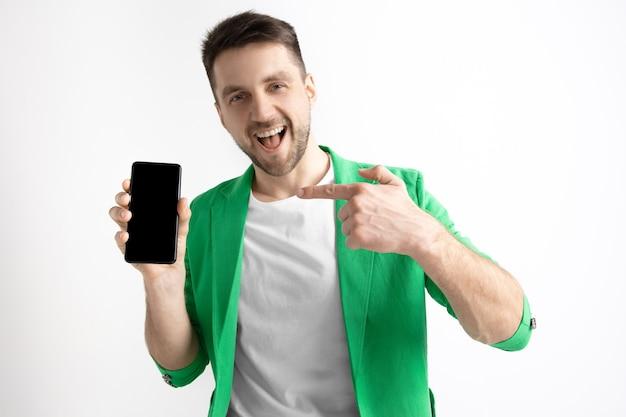 Это круто. хорошие новости. сделай так, как я. молодой красавец показывает экран смартфона и подписывает знак ок, изолированные на сером фоне. человеческие эмоции, выражение лица, рекламная концепция. Бесплатные Фотографии