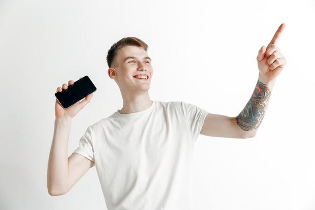 È bello. buone notizie. fallo come me. giovane uomo bello che mostra lo schermo dello smartphone e firma segno ok isolato su sfondo grigio. emozioni umane, espressione facciale, concetto di pubblicità. Foto Gratuite