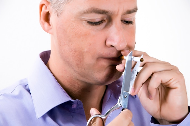 Its time to quit.businessman in purple shirt is cutting a cigarette with scissors. Premium Photo