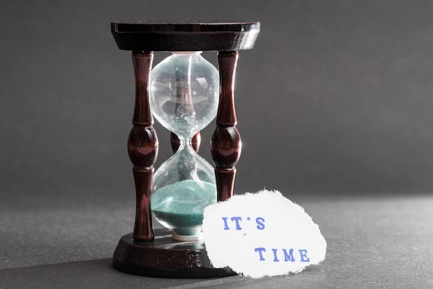 Its time text on torn paper near the hour glass on gray background Free Photo