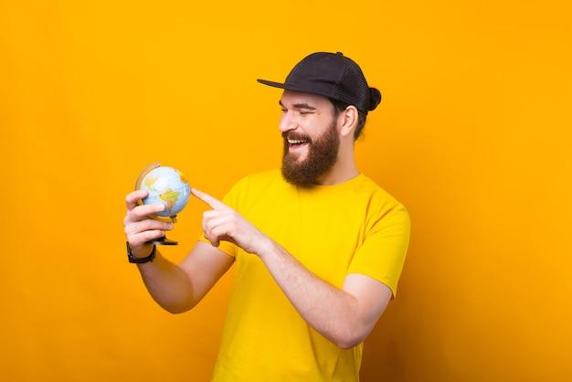 세상을 구할 때입니다. 세계에서 가리키는 젊은 수염 된 Hipster 남자의 사진 프리미엄 사진