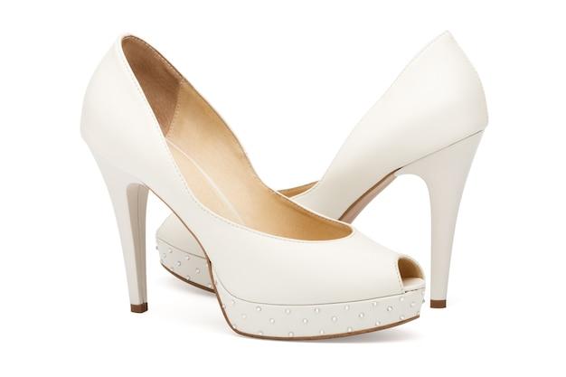 白で分離されたアイボリーの女性の結婚式の靴 Premium写真