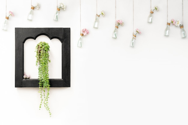 Ivy in black wooden frame on white wall with flowers in hanging bottles. Premium Photo