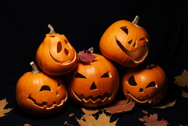 Jack lantern pumpkins for halloween decoration and maple leaves with acorns Premium Photo
