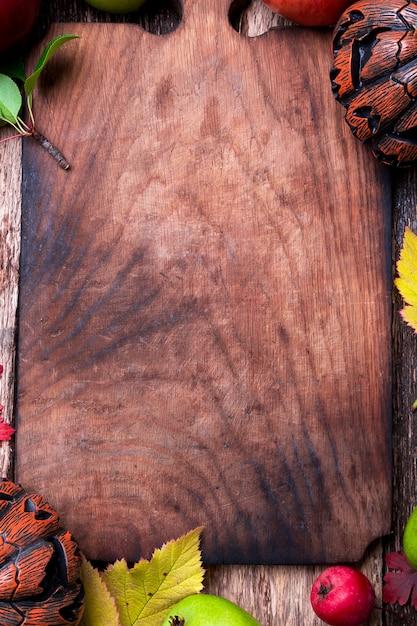 木製の空のまな板の周りのジャック-o-ランタン。秋。ハロウィン。上面図。 copyspace。フレーム。 Premium写真